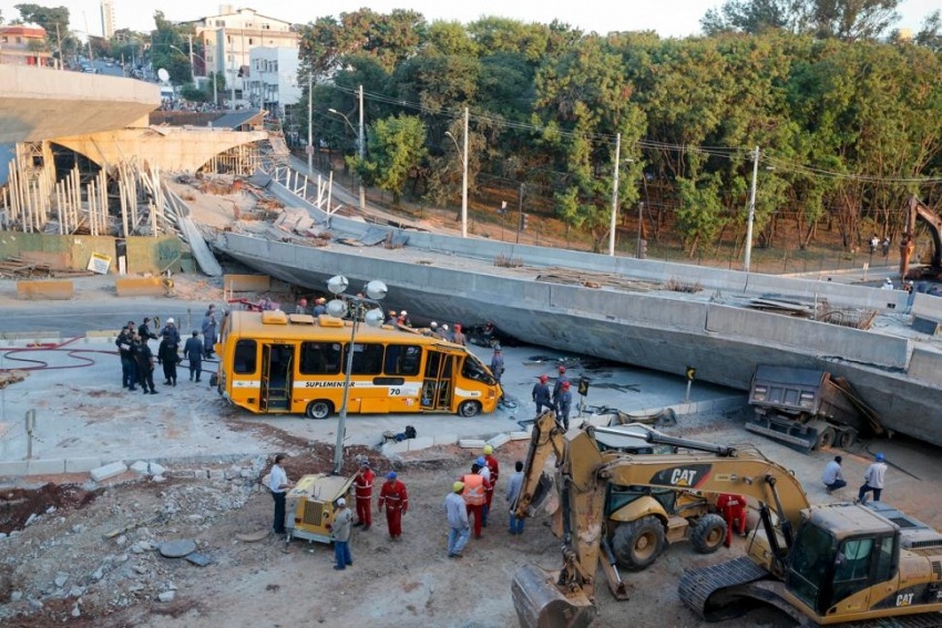A commuter bus and two construction vehicles were trapped under the bridge span
