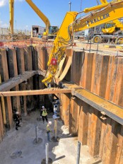 Completed internally-braced sheet piles shown in the background while a rig installs helical piles.
